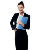 Secretaria sonriente que sostiene el cuaderno espiral fotografía de archivo