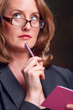 Secretary. Wearing glasses, holding pen and notebook, looking up Stock Images