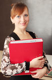 Secretary. Young smiling woman holds the red folder Royalty Free Stock Image
