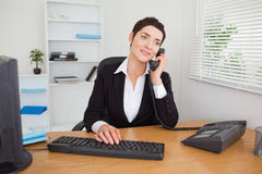 Secretary answering the phone. In her office Royalty Free Stock Photos