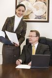 Secretary and boss. Beautiful woman is showing an official record to the sitting man in the suit Royalty Free Stock Image
