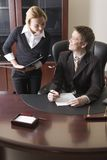 Secretary and boss. Pretty girl with the folder in her hands and man sitting at the table and signing the document Royalty Free Stock Photos