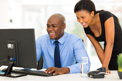 Secretary with boss. Successful african secretary with her boss working on computer Stock Photo