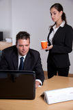 Secretary bringing a cup of coffee Royalty Free Stock Photos
