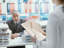 Secretary bringing an envelope to her boss royalty free stock photography