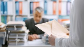 Secretary bringing an envelope to her boss. Assistant bringing mail to her boss, he is working at desk overloaded with paperwork royalty free stock image
