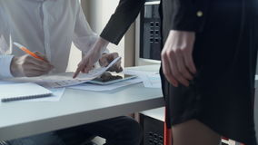 Secretary brings documents to boss caption, which sits at a desk. stock video footage