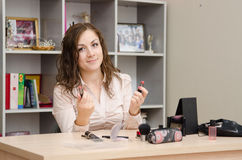 Secretary can not determine the choice of lipstick. Young woman sitting at office table, laid out on the table cosmetics Royalty Free Stock Photos
