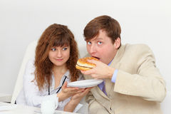 Secretary is feeding his boss at workplace Royalty Free Stock Photo