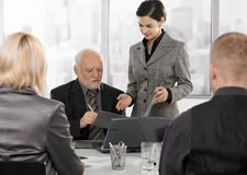 Secretary getting contract to sign by executive. Secretary getting contract to sign by senior executive at businessmeeting Royalty Free Stock Photos