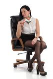 Secretary girl in the chair. Beautiful girl in a mini skirt and white blouse Stock Photo