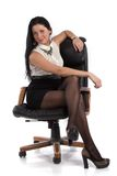Secretary girl in the chair. Beautiful girl in a mini skirt and white blouse Royalty Free Stock Photo