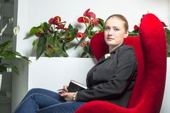 Secretary girl in office with red chair Stock Photo