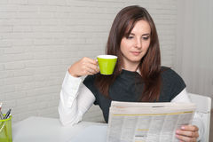 Secretary Girl reading a newspaper holding it in a hand Royalty Free Stock Image