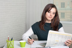 Secretary Girl reads a newspaper, making notes Royalty Free Stock Photo