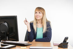Secretary girl thought sitting at her workplace in the office Stock Photos