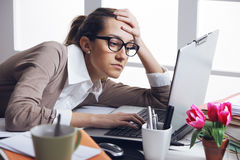 Secretary is having a bad day. Young and beautiful businesswoman tired from work in the office.Woman holding her head Stock Image