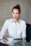 Secretary holding tablet and write on blank paper Royalty Free Stock Photos