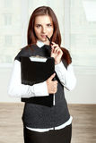 Secretary holds a black folder on your chest and held a pen to h Royalty Free Stock Image