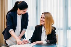Secretary profession assist boss office workspace. Secretary job. professional duties. young employee assisting her boss in signing documents. good working Royalty Free Stock Photo