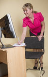 Secretary leaning over her desk Stock Photography