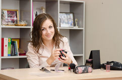 Secretary with lipstick in hand. Young woman sitting at office table, laid out on the table cosmetics Royalty Free Stock Photo