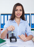Secretary with long dark hair and stamp at office Royalty Free Stock Photos