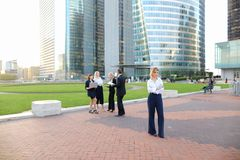 Secretary looking at camera with team members background in La D. Secretary standing in La Defense Paris and looking at camera near speaking employees with boss Royalty Free Stock Photos