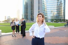 Secretary looking at camera with team members background in La D. Secretary standing in La Defense Paris and looking at camera near speaking employees with boss Royalty Free Stock Image