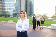 Secretary looking at camera with team members background in La D. Secretary standing in La Defense Paris and looking at camera near speaking employees with boss Royalty Free Stock Photo