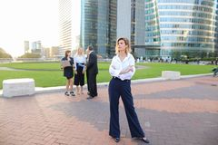 Secretary looking at camera with team members background in La D. Secretary standing in La Defense Paris and looking at camera near speaking employees with boss Stock Photo