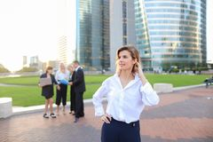 Secretary looking at camera with team members background in La D. Secretary standing in La Defense Paris and looking at camera near speaking employees with boss Royalty Free Stock Photography