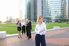 Secretary looking at camera with team members background in La D. Secretary standing in La Defense Paris and looking at camera near speaking employees with boss Stock Images
