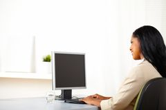 Secretary looking to a monitor. Portrait of a cheerful secretary looking to the monitor screen with copy space Stock Photos