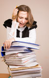 Secretary with a lot of documents. Tired secretary with a lot of documents stock photography