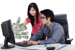 Secretary and manager with money on studio. Picture of a young secretary pointing at money on the computer screen while working together with her manager in the Royalty Free Stock Photography