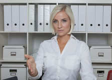 Secretary offers handclasp. Accountnant in white blouse in white office environment offers handshake Royalty Free Stock Photos