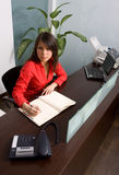 Secretary In The Office. Young Beautifull Secretary dressed in red in The Office Royalty Free Stock Photo