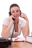 Secretary in office. Whit two phones Stock Image