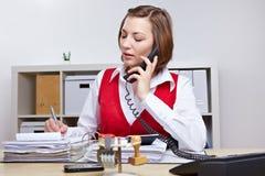 Secretary in office taking notes. Secretary in business office taking notes while talking on the phone Royalty Free Stock Photos