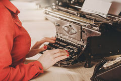 Secretary at old typewriter with telephone. Young woman using ty Stock Photo