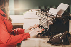 Secretary at old typewriter with telephone. Young woman using ty Stock Image