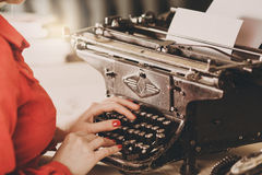 Secretary at old typewriter with telephone. Young woman using ty Royalty Free Stock Photos