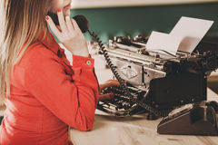 Secretary at old typewriter with telephone. Young woman using ty Stock Images