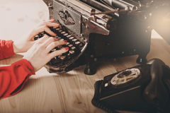 Secretary at old typewriter with telephone. Young woman using ty stock photography