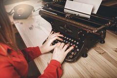 Secretary at old typewriter with telephone. Young woman using ty Stock Photos