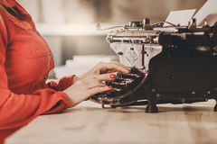 Secretary at old typewriter with telephone. Young woman using ty Royalty Free Stock Images