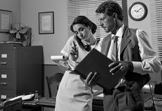 Secretary on the phone taking down notes. Young secretary on the phone and director working together, 1950s vintage style office Royalty Free Stock Photos