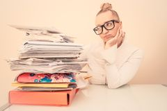 Secretary with pile of documents. Inquiet business woman looking at her stack of documents - Secretary deluged by bills Stock Photos