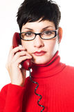 Secretary in red. Beautiful young woman with charming big green eyes is bearing modern glasses and receiving calls on a landline phone Stock Photos